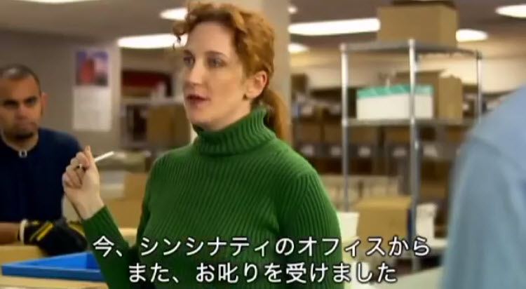 Still from a video -- a woman in a green sweater speaks at a warehouse, with Japanese subtitles in the lower third.